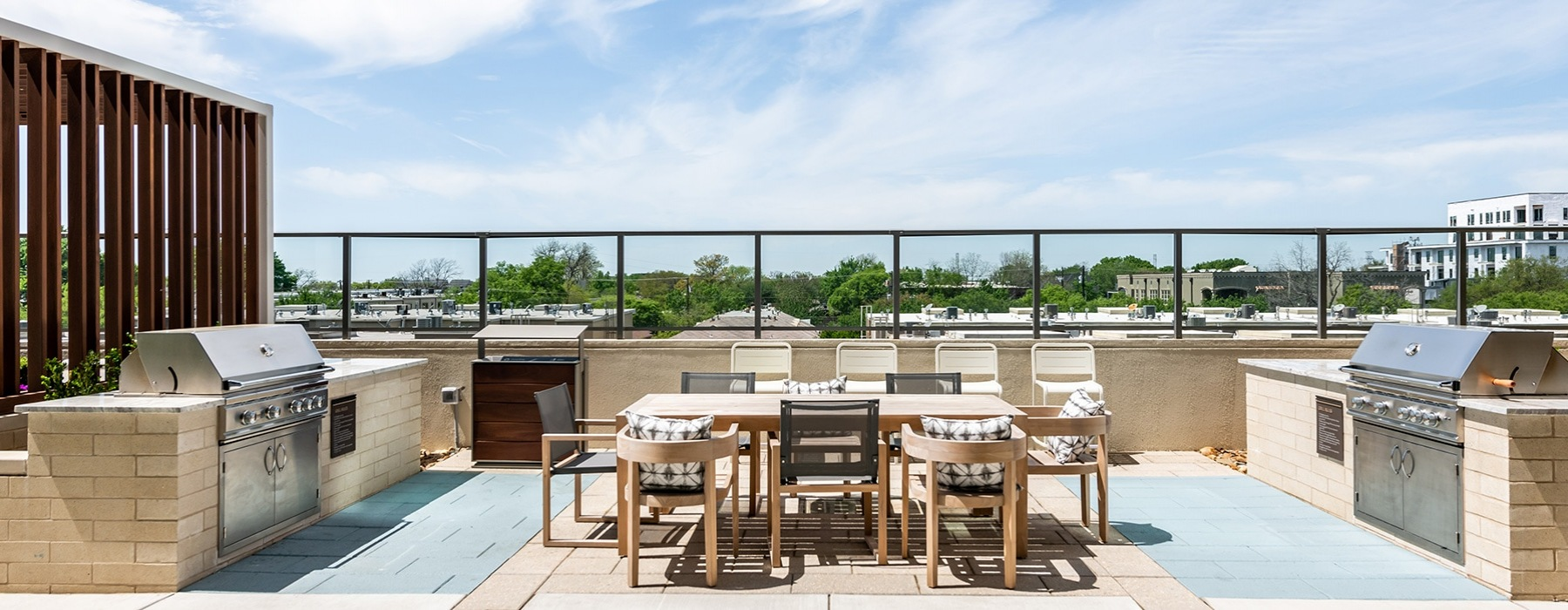 rooftop lounge area with tables, chairs and grill stations