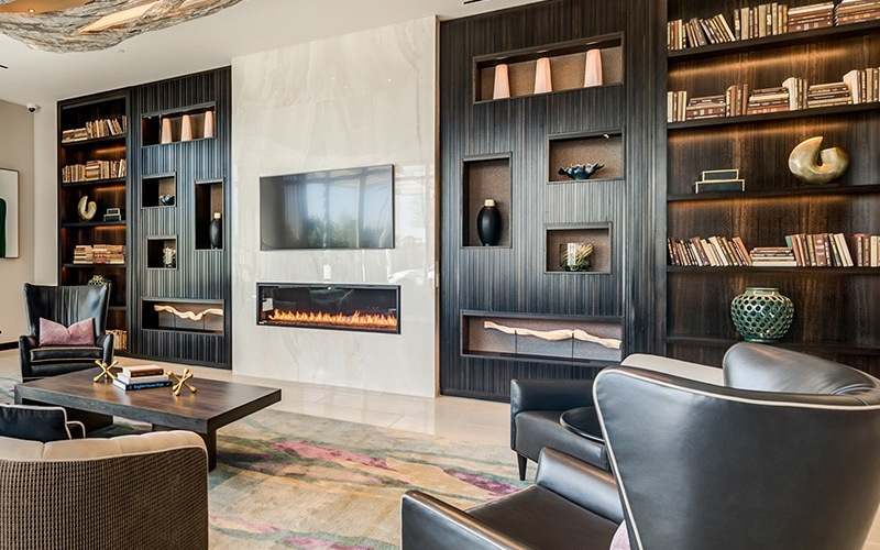 resident lounge and library area with a fireplace and warm accents with leather chairs for seating