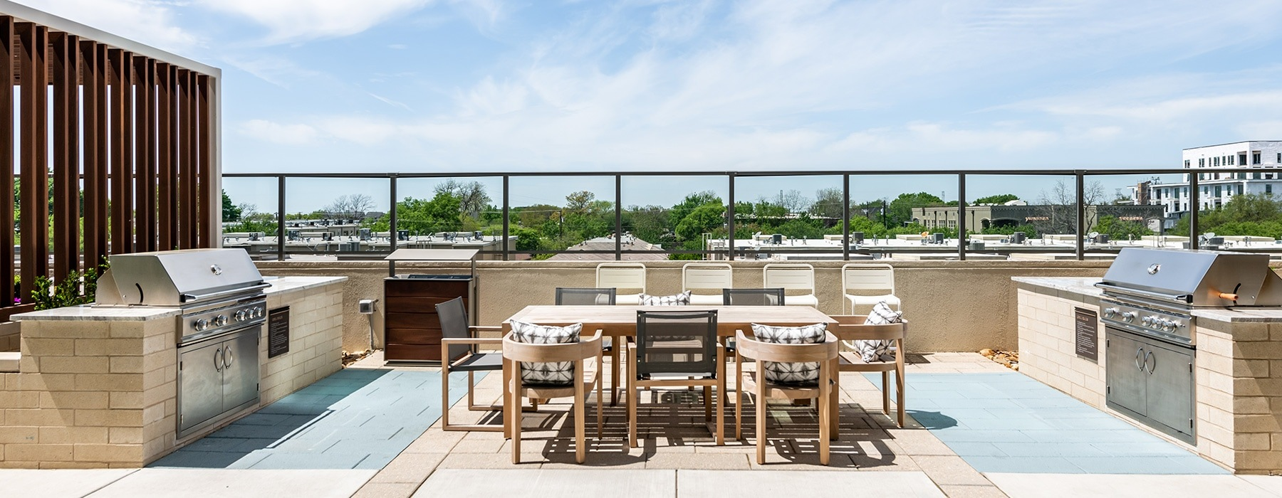 rooftop with community views, tables, chairs for seating and two grill stations