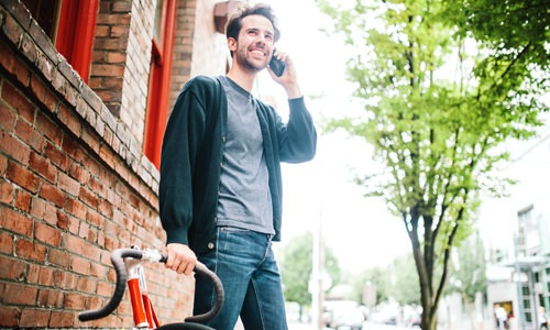 Man on a neighborhood street next to bike talking on his phone and smiling